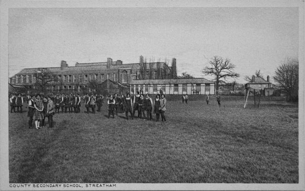 Old photo of school girls in field standing in front of school