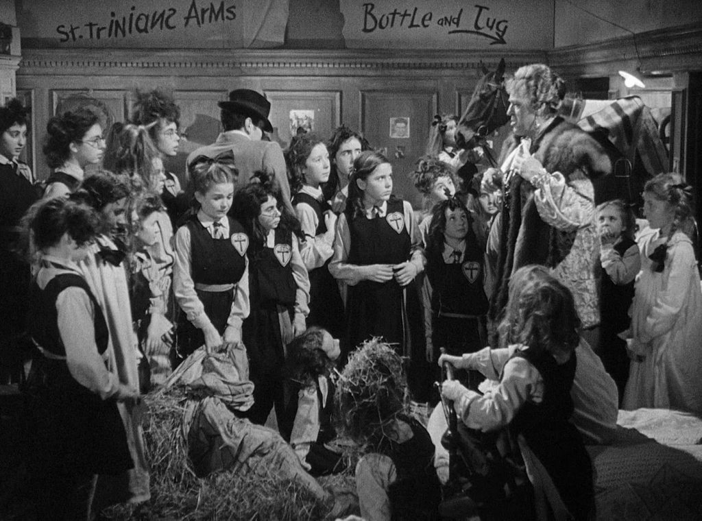 """Scene from the film """"Belles of St Trinians"""". Schoolgirls crowded into a room with a horse being lectured to by their headmistress."""